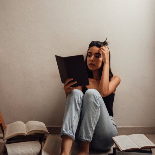 woman in black tank top and denim jeans reading a book